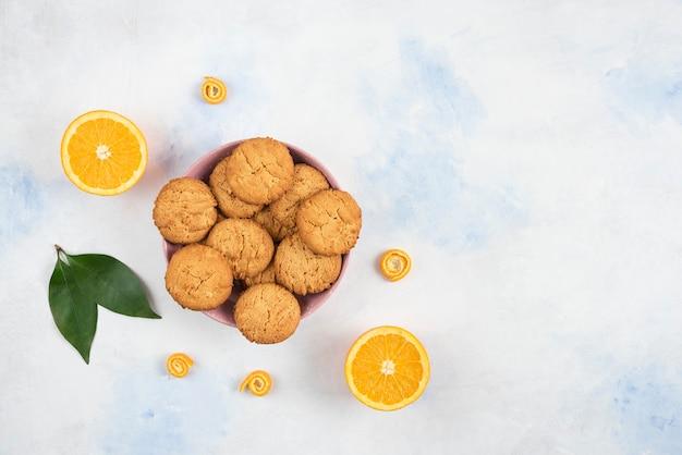Bovenaanzicht van zelfgemaakte koekjes met half gesneden sinaasappel over witte tafel.