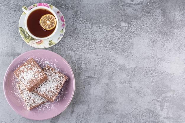 Bovenaanzicht van zelfgemaakte koekjes met kopje geurige thee op grijs.