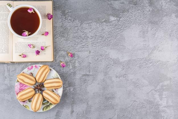 Bovenaanzicht van zelfgemaakte koekjes met kopje thee en boek op grijs.