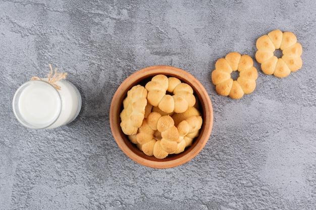 Bovenaanzicht van zelfgemaakte koekjes met melk op grijs.