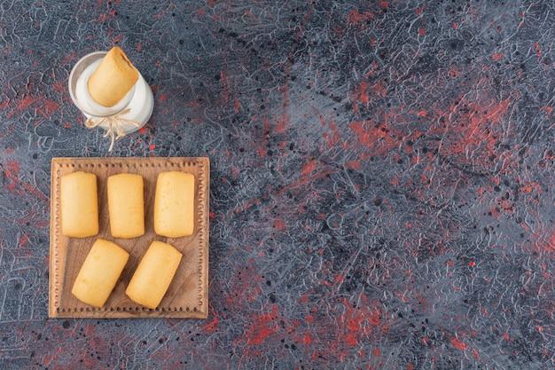 Bovenaanzicht van zelfgemaakte koekjes met melk op rustiek.