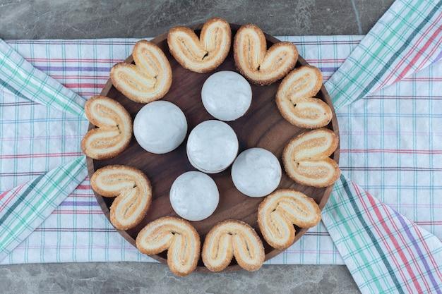 Bovenaanzicht van zelfgemaakte koekjes op een houten bord.