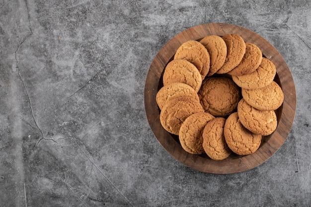 Bovenaanzicht van zelfgemaakte koekjes op houten dienblad over grijze tafel.