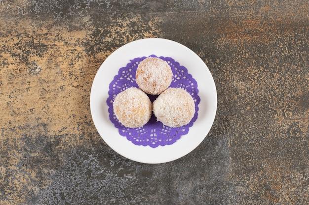 Bovenaanzicht van zelfgemaakte koekjes op plaat over rustieke tafel.