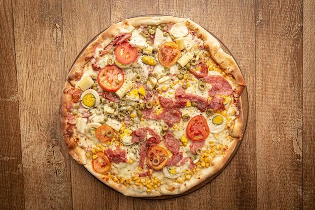 Bovenaanzicht van zelfgemaakte pizza met tomaat, olijf, kaas en andere ingrediënten.
