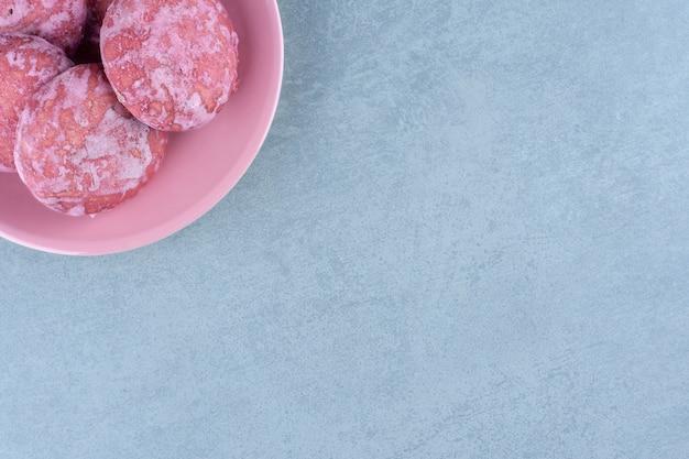 Bovenaanzicht van zelfgemaakte roze koekjes in roze kom.