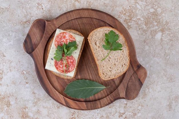 Bovenaanzicht van zelfgemaakte salami sandwiches op houten dienblad.