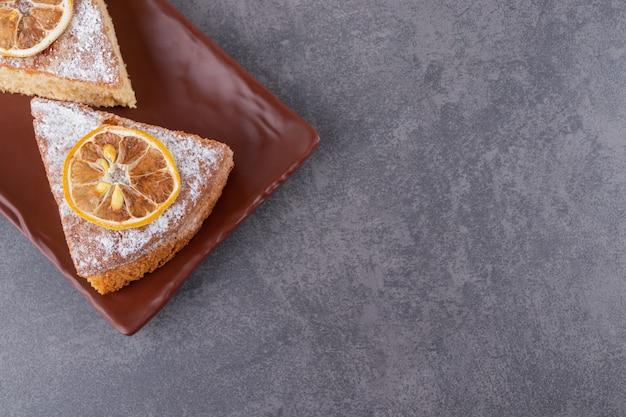 Bovenaanzicht van zelfgemaakte taart segmenten op bruine plaat.