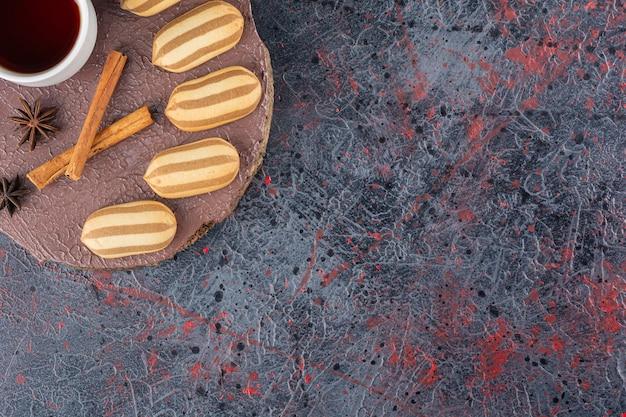Bovenaanzicht van zelfgemaakte verse koekjes met kopje thee op rustiek.