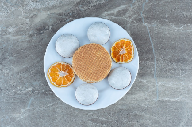 Bovenaanzicht van zelfgemaakte verse koekjes met wafel en droge stukjes sinaasappel.