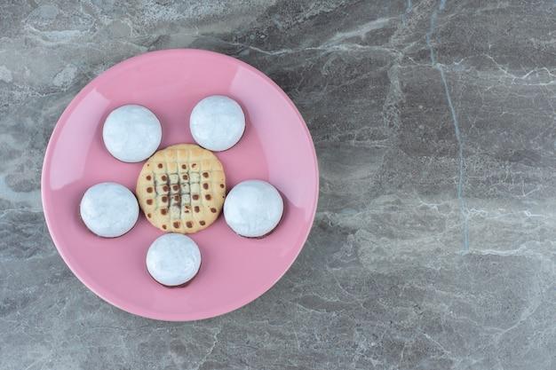 Bovenaanzicht van zelfgemaakte verse koekjes op roze plaat.
