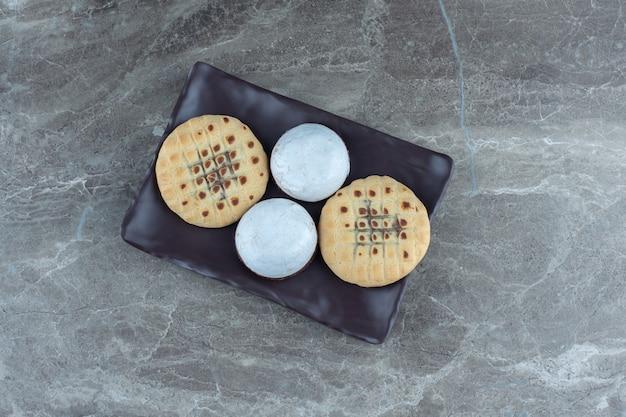 Bovenaanzicht van zelfgemaakte verse koekjes op zwarte plaat.