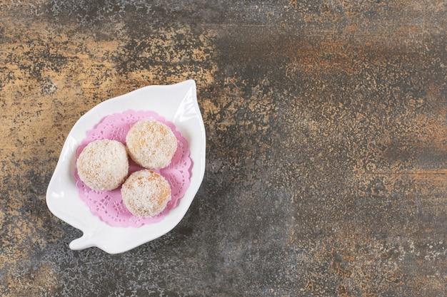 Bovenaanzicht van zelfgemaakte verse lekkere koekjes op witte plaat over rustieke tafel.