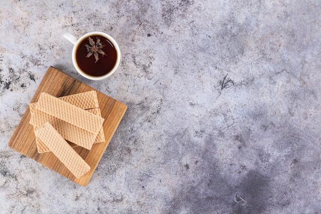 Bovenaanzicht van zelfgemaakte wafels met geurige thee op grijs