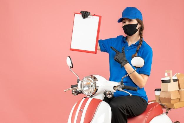 Bovenaanzicht van zelfverzekerd koeriersmeisje met een medisch masker en handschoenen zittend op een scooter met een leeg vel papier dat bestellingen aflevert op een pastelkleurige perzikachtergrond