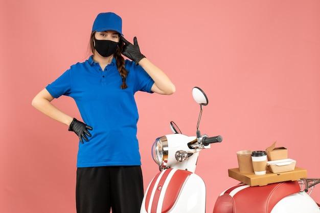 Bovenaanzicht van zelfverzekerd koeriersmeisje met medisch masker dat naast de motorfiets staat met koffiecake erop op een pastelkleurige perzikkleurige achtergrond