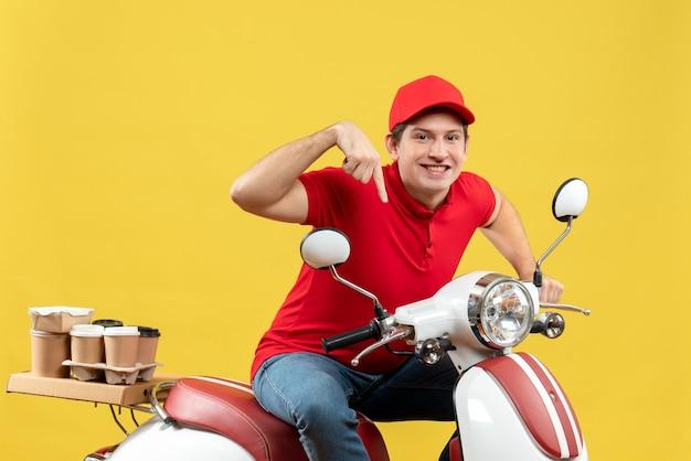 Bovenaanzicht van zelfverzekerde glimlachende jonge volwassene die rode blouse en hoed draagt en bestellingen levert die naar beneden wijzen op een gele achtergrond