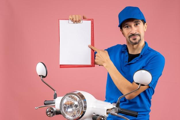 Bovenaanzicht van zelfverzekerde mannelijke bezorger met hoed zittend op scooter met document scooter