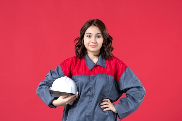 Bovenaanzicht van zelfverzekerde vrouwelijke bouwer in uniform en met harde hoed op geïsoleerde rode achtergrond