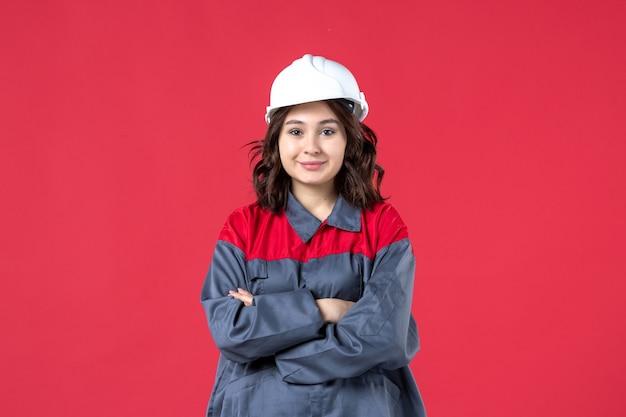Bovenaanzicht van zelfverzekerde vrouwelijke bouwer in uniform met helm op geïsoleerde rode achtergrond
