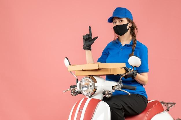 Bovenaanzicht van zelfverzekerde vrouwelijke koerier met een medisch masker en handschoenen die op een scooter zitten en bestellingen afleveren die naar boven wijzen op een pastelkleurige perzikachtergrond