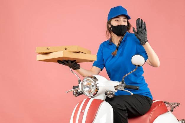 Bovenaanzicht van zelfverzekerde vrouwelijke koerier met een medisch masker en handschoenen die op een scooter zitten en bestellingen afleveren op een pastelkleurige perzikachtergrond