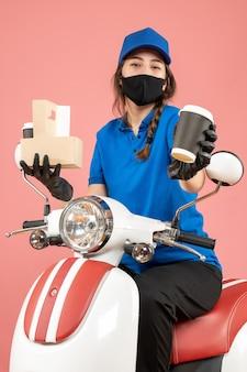 Bovenaanzicht van zelfverzekerde vrouwelijke koerier met een zwart medisch masker en handschoenen die bestellingen afleveren op perzikachtergrond