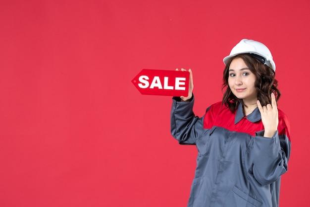 Bovenaanzicht van zelfverzekerde vrouwelijke werknemer in uniform die een harde hoed draagt en een verkooppictogram aanwijst dat overwinningsgebaar maakt op geïsoleerde rode achtergrond