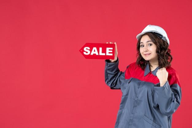 Bovenaanzicht van zelfverzekerde vrouwelijke werknemer in uniform die een harde hoed draagt en een verkooppictogram aanwijst op geïsoleerde rode achtergrond