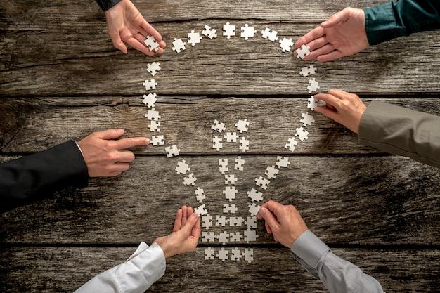 Bovenaanzicht van zes zakenmensen, mannelijk en vrouwelijk, die een gloeilampvorm van kleine puzzelstukjes assembleren op een gestructureerd rustiek houten bureau.