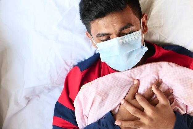 Bovenaanzicht van zieke mannen met chirurgisch gezichtsmasker op bed hand op de borst te zetten.