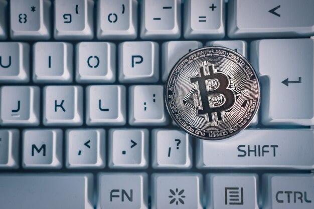 Bovenaanzicht van zilveren bitcoin op een wit toetsenbord