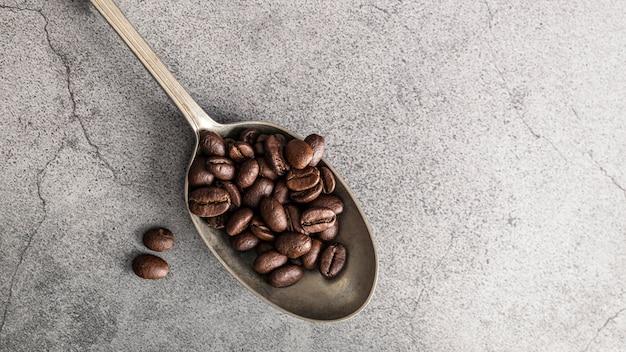 Bovenaanzicht van zilveren lepel met koffiebonen