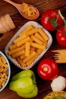 Bovenaanzicht van ziti pasta in kom met spaghetti en rotini soorten in kom en lepel zout tomaat knoflook peper op houten oppervlak
