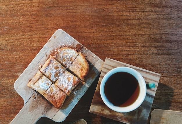 Bovenaanzicht van zoet brood dient op een snijplank met hete thee. leg op houten tafel met kopie ruimte