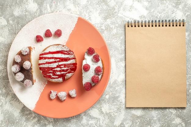 Bovenaanzicht van zoet dessert met saus erop en bessen met blocnote aan zijkant op marmeren achtergrond