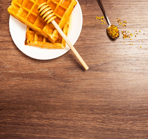 Bovenaanzicht van zoete belgische wafel met honing en bijenpollen