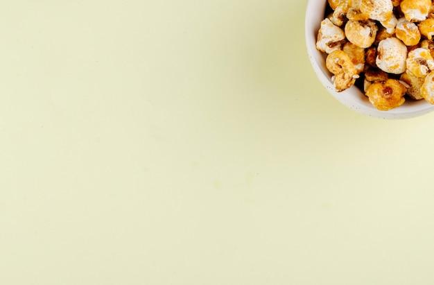 Bovenaanzicht van zoete gekarameliseerde pop corn in een kom op witte achtergrond met kopie ruimte