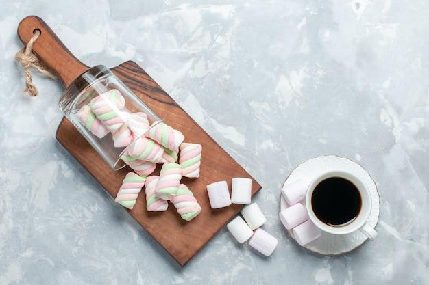Bovenaanzicht van zoete gekleurde marshmallows met kopje thee op lichte witte ondergrond