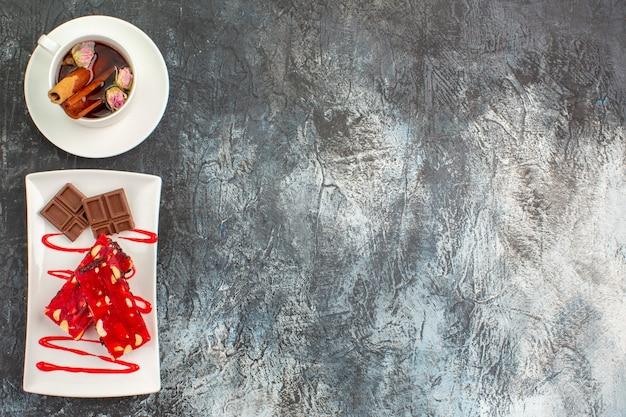 Bovenaanzicht van zoete heerlijke chocolaatjes op witte plaat met een kopje kruidenthee op grijze grond