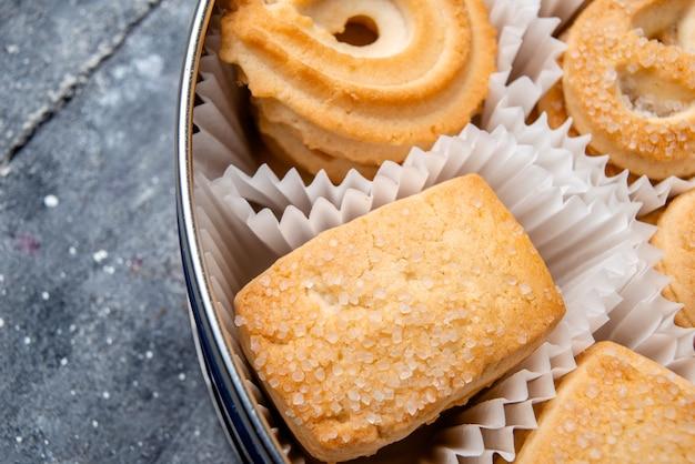 Bovenaanzicht van zoete heerlijke koekjes anders gevormd binnen rond pakket op grijs