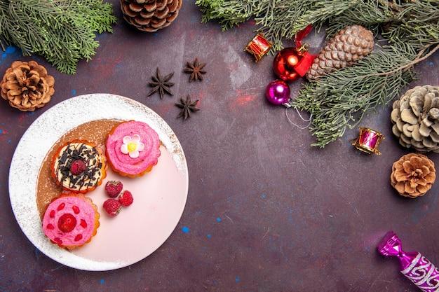 Bovenaanzicht van zoete heerlijke taarten met room en fruit op zwart