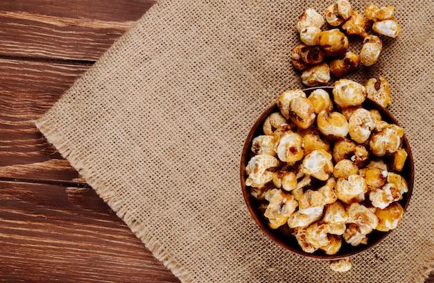 Bovenaanzicht van zoete karamel popcorn in een houten kom op zak op rustieke achtergrond met kopie ruimte