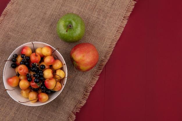 Bovenaanzicht van zoete kers met zwarte bessen in een kom met appels op een rode ondergrond