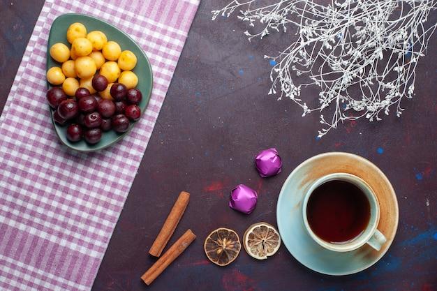 Bovenaanzicht van zoete kersen samen met kaneel en kopje thee op het donkere oppervlak