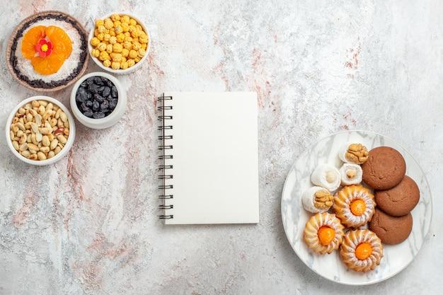 Bovenaanzicht van zoete koekjes met noten en dessert op wit