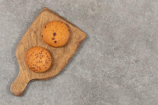 Bovenaanzicht van zoete koekjes op houten snijplank.
