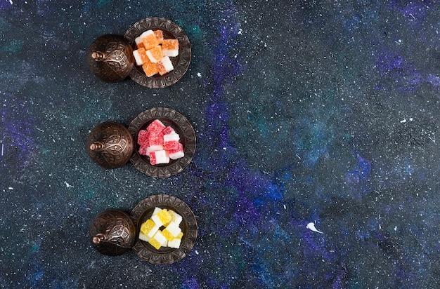 Bovenaanzicht van zoete snoepjes. kleurrijke marmelade op blauwe ondergrond