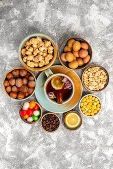 Bovenaanzicht van zoete snoepjes met noten en kopje thee op witte ondergrond