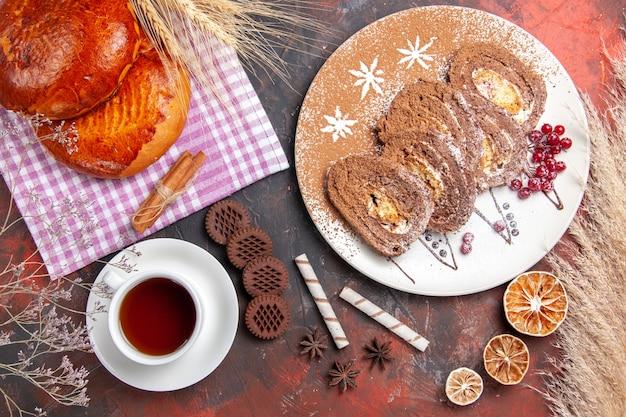 Bovenaanzicht van zoete taarten met thee en koekjesbroodjes